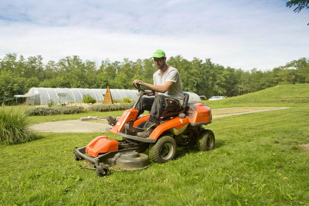 Mann auf Rasenmähertraktor beim Rasenmähen