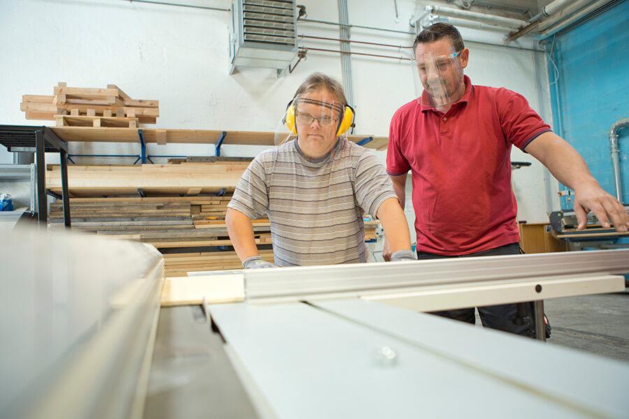 Klient und Betreuer bei Holzarbeiten