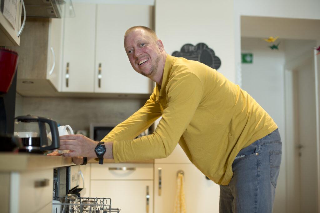 junger Mann räumt Geschirrspüler aus